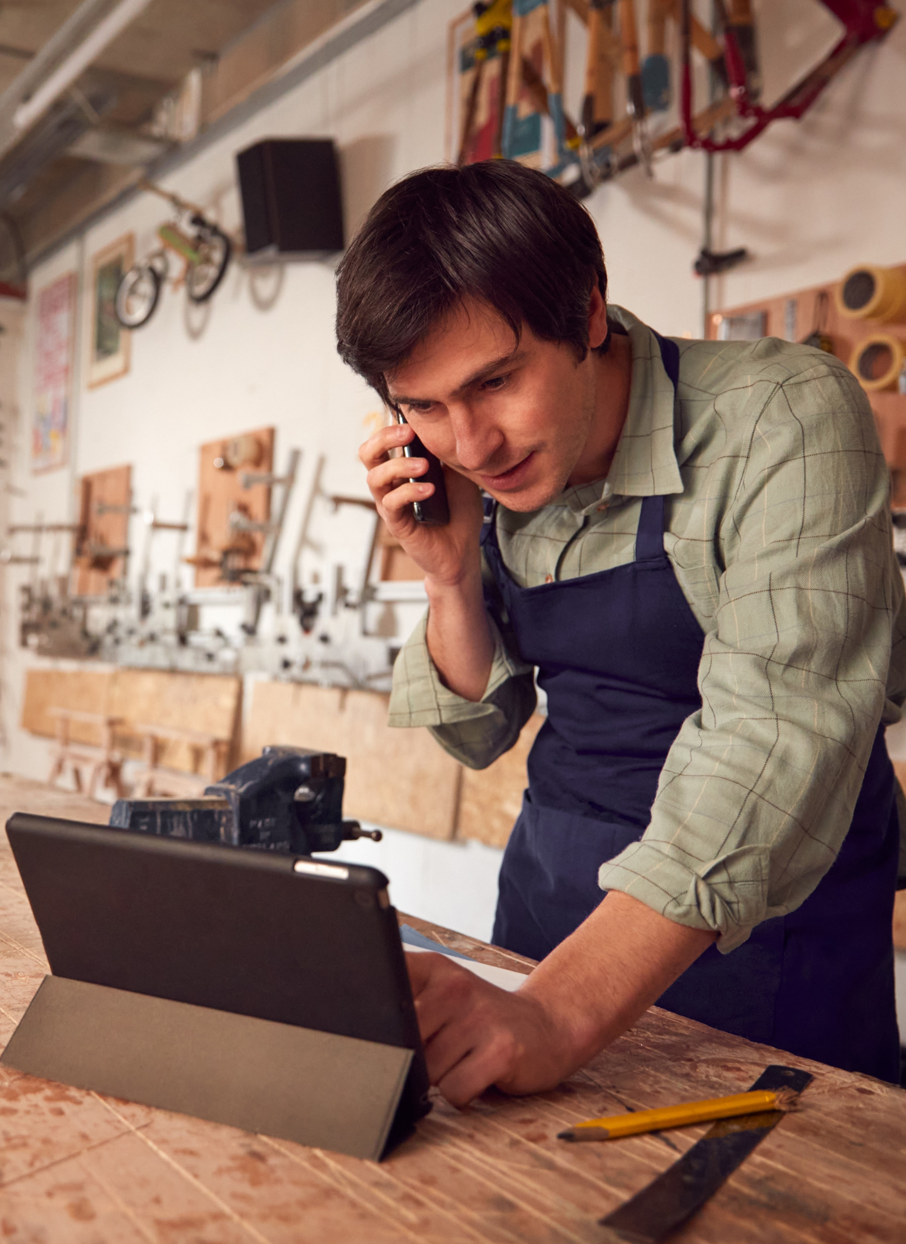 Male Business Owner In Workshop Using Digital Tablet And Making Call On Mobile Phone