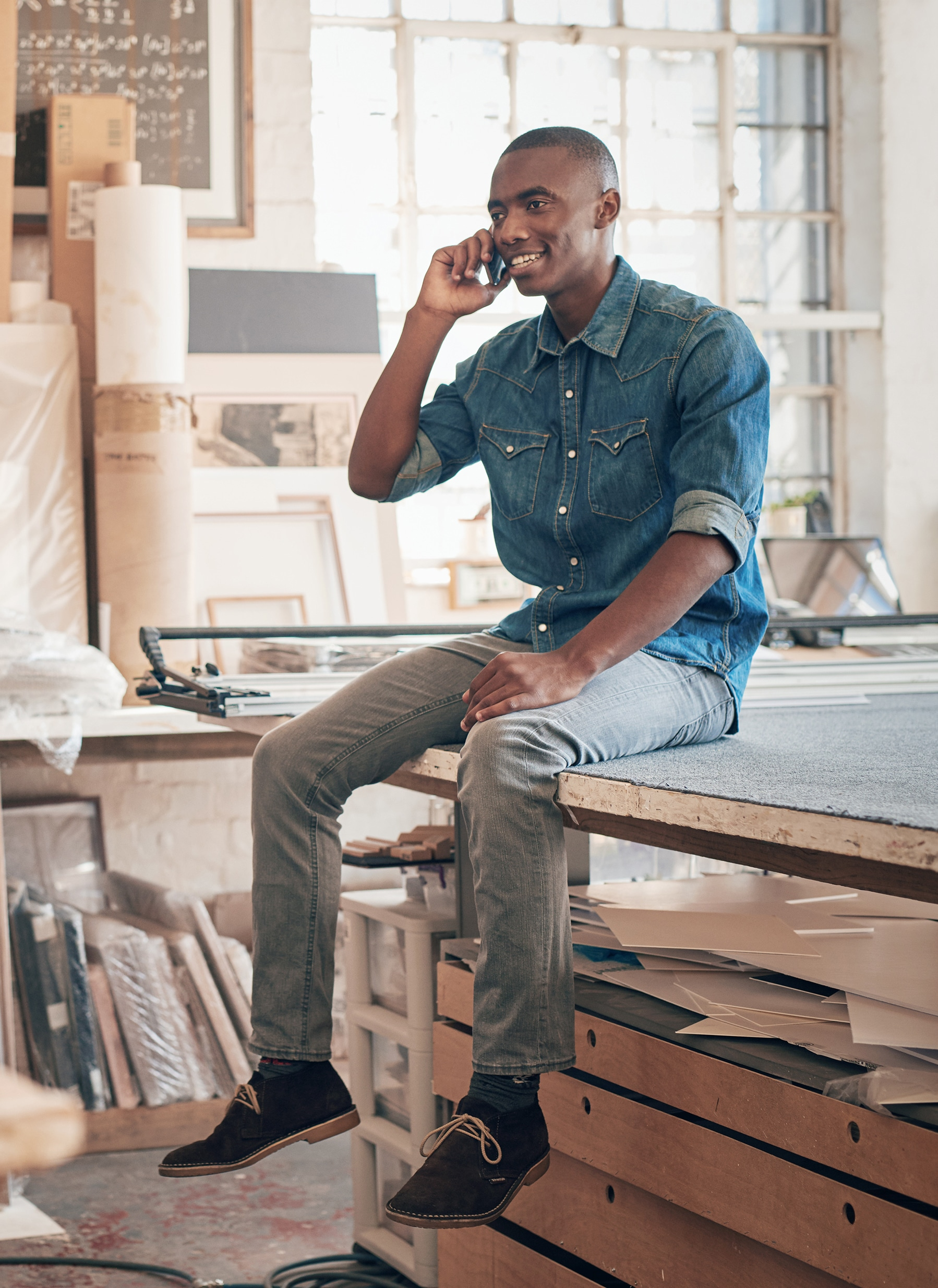 Handsome African designer talking on phone in his studio